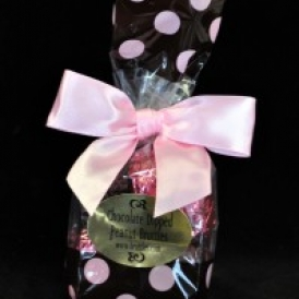 6 Pc Peanut Bruttle Bag.  Bruttles are wrapped in pink and brown foil and put into a brown cello bag with pink polka dots and closed with a pink satin ribbon.
