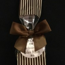 6 Pc Cashew Bruttle Bag.  Cashew Bruttles wrapped in silver foil and put into a cream colored cello bag with brown polka dots and closed with a brown satin bow.