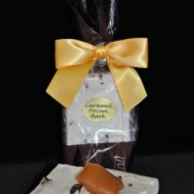 Caramel Pecan Bark in a clear and brown cello bag with a brown satin bow