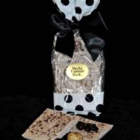 Mocha Espresso Bark in a white and clear cello bag with black polka dots and closed with a black satin bow