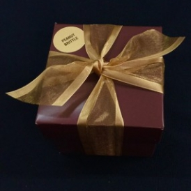 8 ounces Old Fashioned Peanut Brittle in a gold and white stripped box with gold ribbon